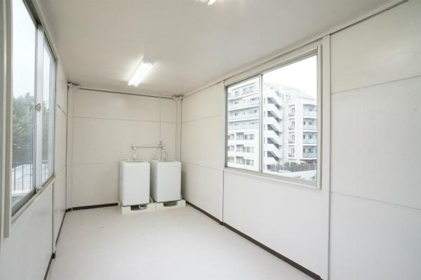 屋上のプレハブに洗濯機が設置されています。雨に濡れません。