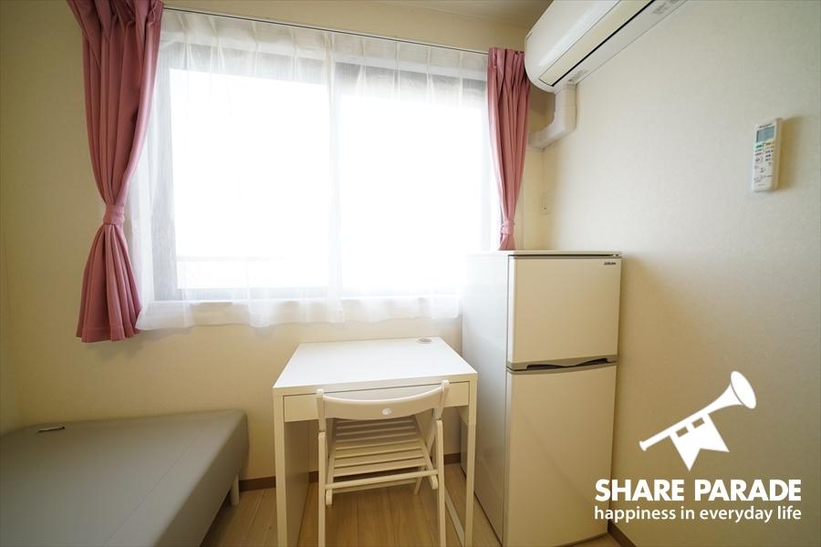 窓の前に机と椅子があります。